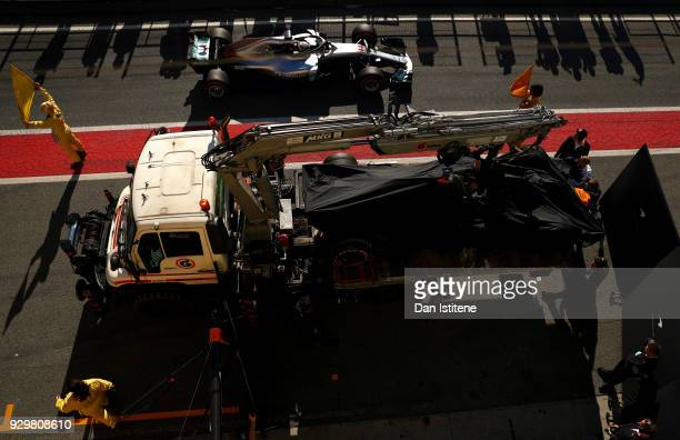 The car of Fernando Alonso of Spain and McLaren F1 is returned to the pits after stopping on track during day four of F1 Winter Testing at Circuit de...