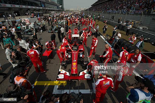 The car of Ferrari driver Fernando Alonso of Spain is prepared on the starting grid of the Formula One Chinese Grand Prix in Shanghai on April 14...