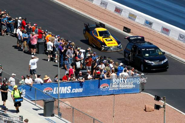 The car of JR Todd Toyota Camry NHRA Funny Car is towed down the return road past fans in the beer garden during the 19th Annual DENSO Spark Plugs...