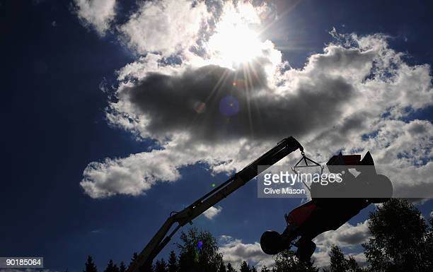 The car of Lewis Hamilton of Great Britain and McLaren Mercedes is lifted from the track following his collision with Jaime Alguersuari of Spain and...