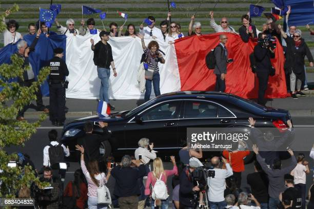 The car of newlyelected French President Emmanuel Macron drives by a Flash Mob of proEurope demonstrators on the way to the Chancellery before a...