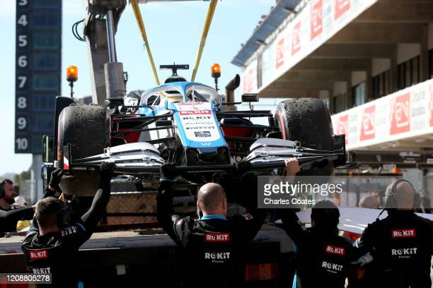 The car of Nicholas Latifi of Canada and Williams is returned to the pits after he stopped on track during Day One of F1 Winter Testing at Circuit de...