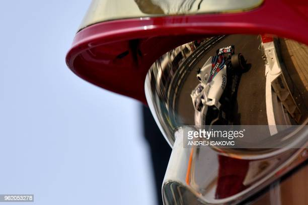 The car of William's Canadian driver Lance Stroll is reflected in a helmet visor after the first practice session at the Monaco street circuit on May...