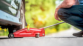 The car,  road, repair and a concept of accident - the driver of people lift in the way the car by means of a  track jack