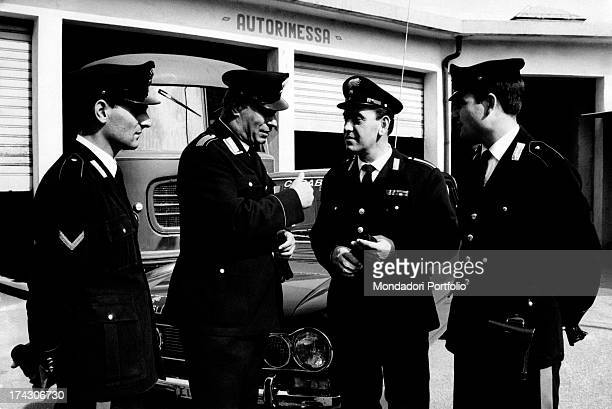 The carabinieri Giuseppe Giordano and Luigi Morabito and the marshals Domenico Colli and Nicola Sganga chatting in front af a garage The four...