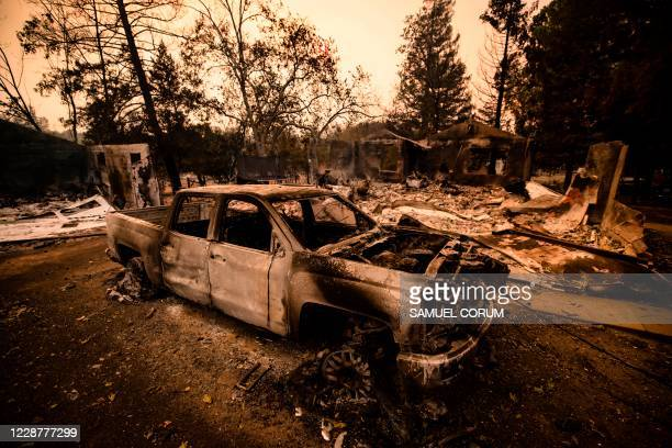 The carcass of a burned car is seen next next to a house reduced to ashes by the Glass Fire in Napa Valley, California on September 28, 2020. - The...