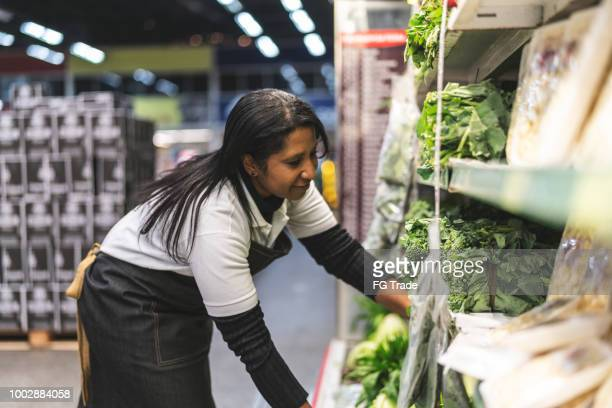 the care of saleswoman with vegetables at supermarket - megastore stock photos and pictures