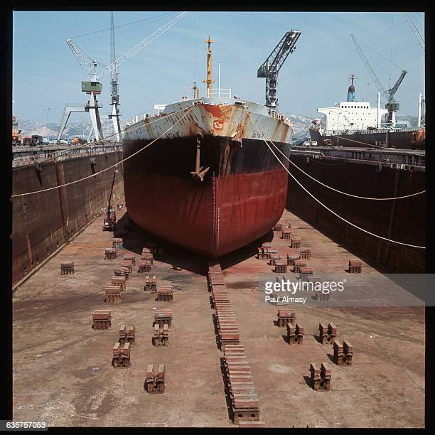 The cargo ship Altair rests in drydock in Marseilles France Another freighter is visible in the next dock Three cranes stand over the shipyard