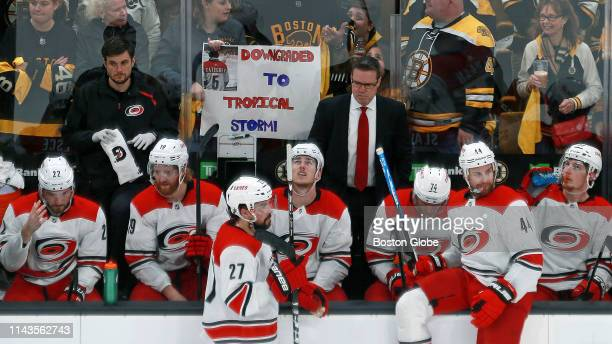 The Carolina Hurricanes bench looks on during the second period as a Boston fan in the background holds a sign reading Downgraded To Tropical Storm...