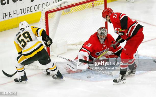 The Carolina Hurricanes' Cam Ward and Brett Pesce stop the Pittsburgh Penguins' Jake Guentzel from scoring during the third period at PNC Arena in...