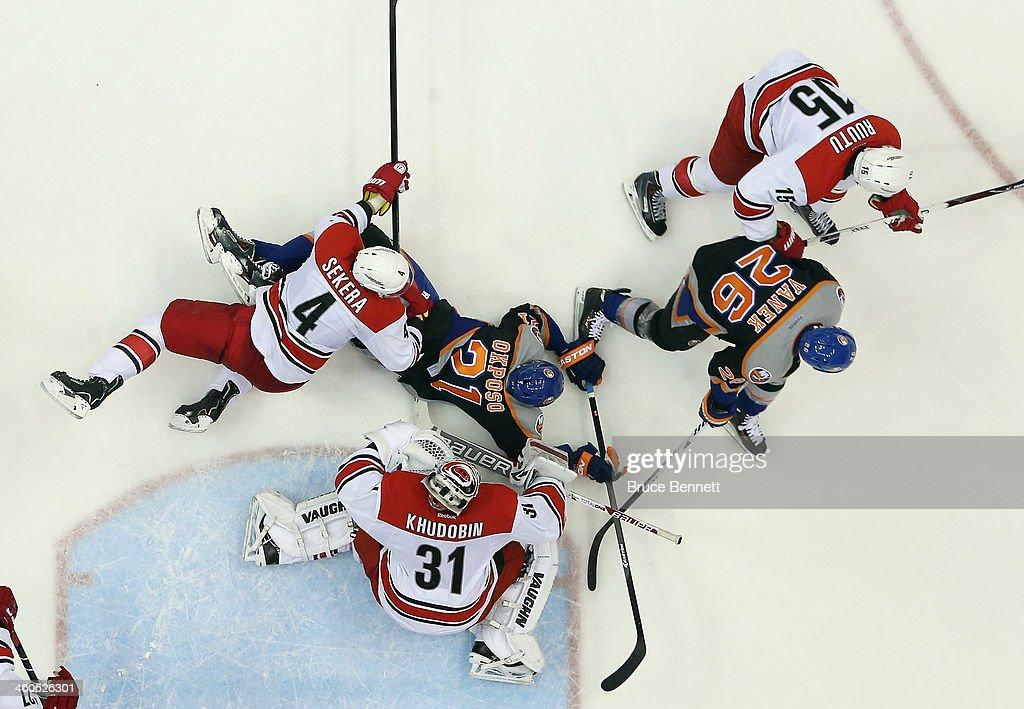 The Carolina Hurricanes defend against Kyle Okposo #21 and Thomas Vanek #26 of the New York Islanders at the Nassau Veterans Memorial Coliseum on January 4, 2014 in Uniondale, New York. The Hurricanes defeated the Islanders 3-2.