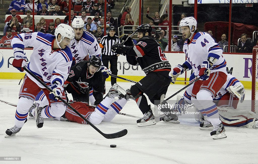 The Carolina Hurricanes' Drayson Bowman (21) and Chad LaRose (59) battle against the New York Rangers' Derick Brassard (16), Brian Boyle (22), Steve Eminger (44) and Henrik Lundqvist (30) during the first period at the PNC Arena in Raleigh, North Carolina, on Saturday, April 6, 2013.
