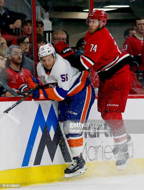 The Carolina Hurricanes' Jaccob Slavin collides with the New York Islanders' Tanner Fritz along the boards during the second period at PNC Arena in...