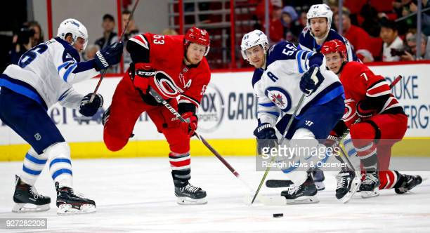 The Carolina Hurricanes' Jeff Skinner and Derek Ryan battle the Winnipeg Jets' Blake Wheeler Mark Scheifele and Josh Morrissey for the puck during...