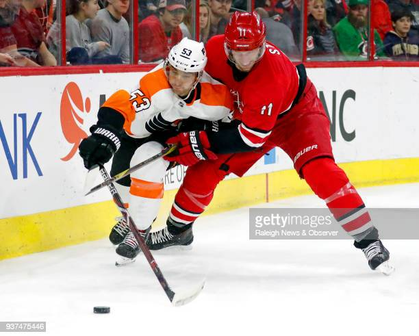 The Carolina Hurricanes' Jordan Staal and the Philadelphia Flyers' Shayne Gostisbehere vie for the puck at PNC Arena in Raleigh NC on March 17 2018