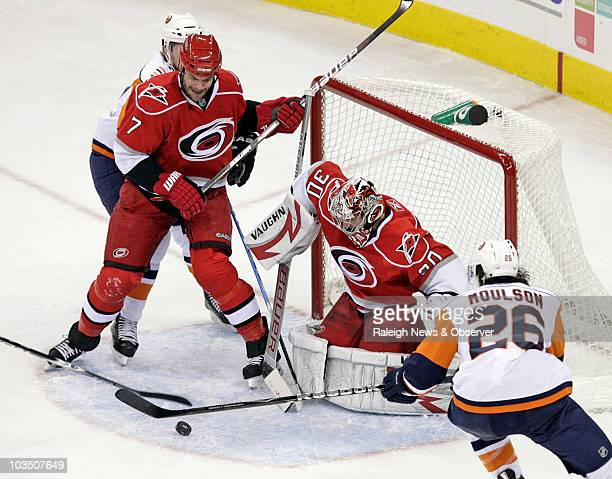 The Carolina Hurricanes' Niclas Wallin and goalie Cam Ward conspire against the New York Islanders' Josh Bailey and Matt Moulson to keep the puck out...