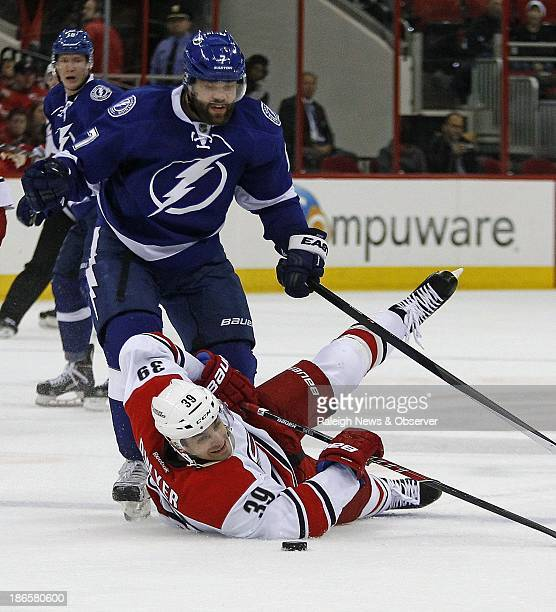 The Carolina Hurricanes' Patrick Dwyer and the Tampa Bay Lightning's Radko Gudas go for the puck during the first period at the PNC Arena in Raleigh...