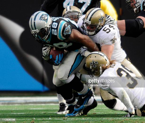 The Carolina Panthers' Jonathan Stewart drags New Orleans Saints defenders Marvin Mitchell Troy Evans and Chris Reis for yards during secondquarter...