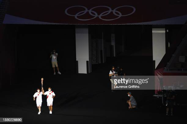 The carrier of the torch makes their way to the Cauldron during the Opening Ceremony of the Tokyo 2020 Olympic Games at Olympic Stadium on July 23,...