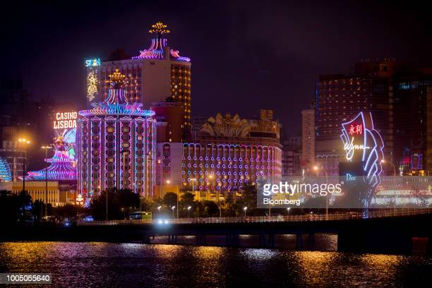 The Casino Lisboa, operated by SJM Holdings Ltd., left, stands next to signage for Wynn Resorts Ltd.'s Wynn Macau casino resort at night in Macau,...