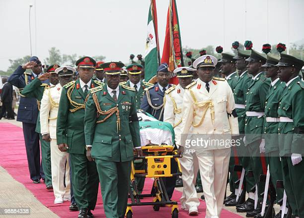 The casket containing the body of late Nigerian President Umaru Yar'Adua is stetchered at Abuja airport on May 6 2010 Dozens of armed soldiers and...