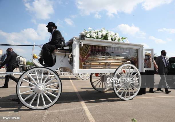 The casket containing the remains of George Floyd are loaded onto a horse drawn hearse during a funeral procession on June 9 2020 in Houston Texas...