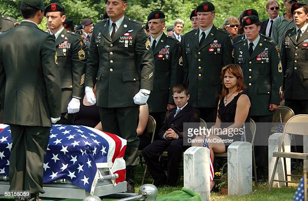 The casket of Army Staff Sgt. Christopher Piper is prepared for burial as wife Connie and son Christopher look June 27, 2005 during his funeral in...