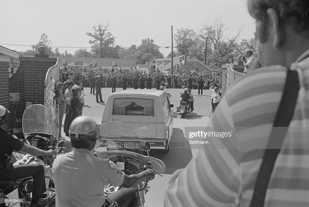 The casket of Elvis Presley can be seen through the back window of the hearse as it passes out the front gate of the Presley mansion past saluting policemen, while thousands of fans watch from across the street.
