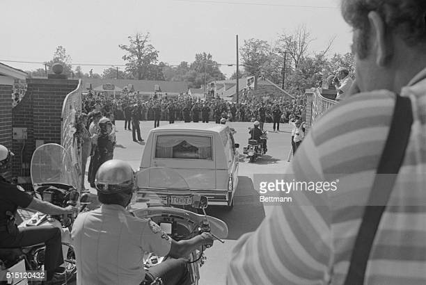 The casket of Elvis Presley can be seen through the back window of the hearse as it passes out the front gate of the Presley mansion past saluting...