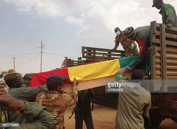 The caskets wrapped in the Malian flag containing the remains of the victims of the January 18 suicide attack on a military camp in Goa are lifted...