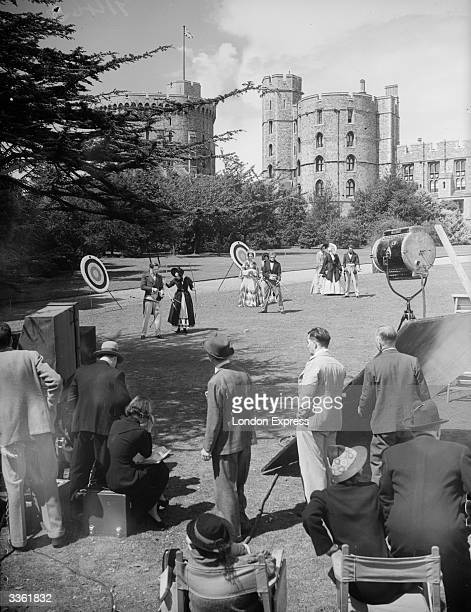 The cast and crew of 'Sixty Glorious Years' filming on the lawns at Windsor Castle The two actors nearest camera are Anna Neagle and Anton Walbrook...