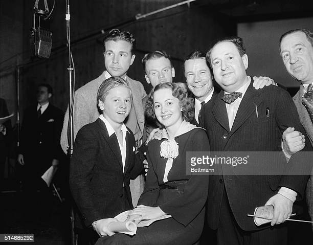 The cast of A Midsummer Night's Dream gather together with Warner Brothers executives Olivia de Havilland Mickey Rooney Dick Powell and James Cagney...
