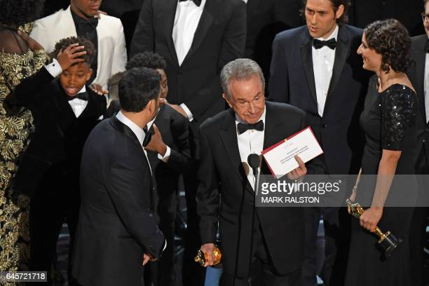 TOPSHOT The cast of 'Moonlight' and ''La La Land' appear on stage as presenter Warren Beatty shows the winner's envelope for Best Movie 'Moonlight'...
