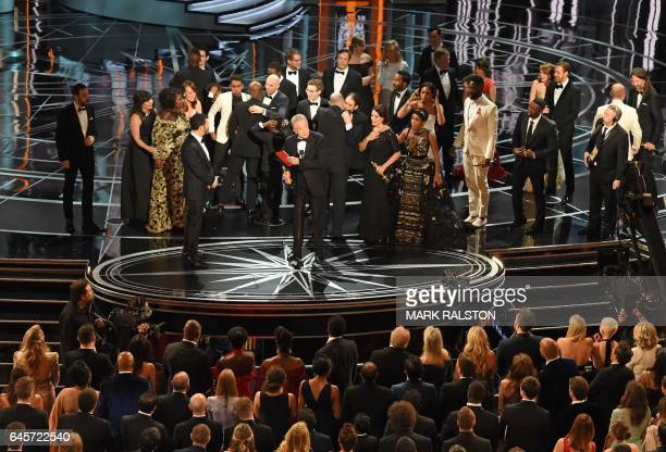The cast of Moonlight and La La Land appear on stage as presenter Warren Beatty flanked by host Jimmy Kimmel shows the winner's envelope for Best...