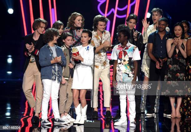The cast of 'Stranger Things' accepts Show of the Year from the cast of '13 Reasons Why' onstage during the 2017 MTV Movie And TV Awards at The...