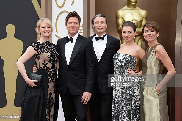 The cast of The Hunt arrives on the red carpet for the 86th Academy Awards on March 2nd 2014 in Hollywood California AFP PHOTO / Robyn BECK