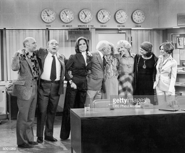 The cast of 'The Mary Tyler Moore Show' stands with their arms around each other in the newsroom in a promotional portrait for the series finale LR...