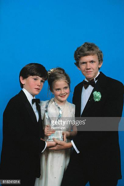 The cast of the movie ET with the People's Choice Award that they won for favorite Motion Picture Holding the award are Henry Thomas Drew Barrymore...