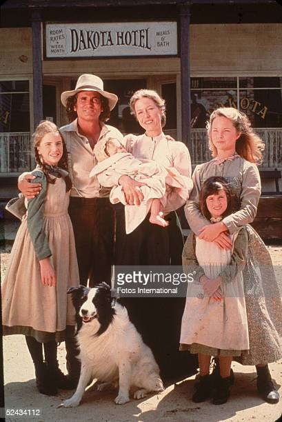 The cast of the television series 'Little House on the Prairie' with a dog on the set of the show, mid 1970s. Clockwise from left: American actors...