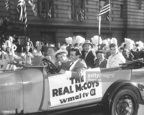 The cast of the televison comedy 'The Real McCoys' drive down Pennsylvania Avenue in an opentop car similiar to one used in the show Washington DC...