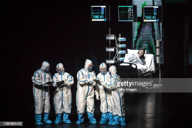 The cast wear personal protective equipment as they perform as medical staff on stage during the opera Angel's Diary on October 18 2020 in Wuhan...