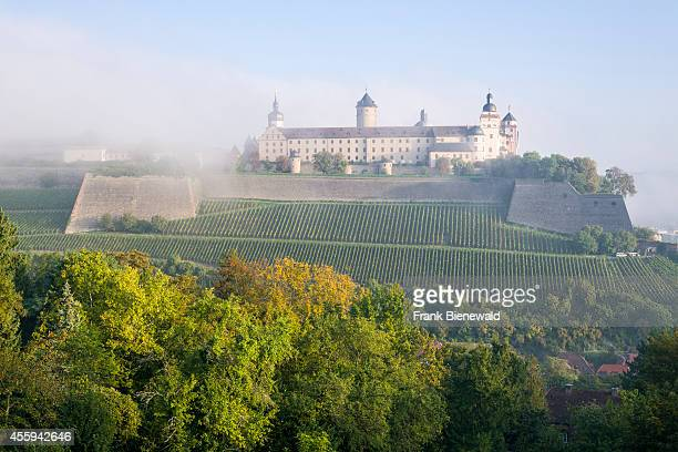 The castle 'Festung Marienberg' is located on a hill above the town shining through the morning fog