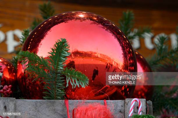 The Castle Square is reflected in a Christmas tree decoration bowl in Stuttgart, southern Germany, on November 30 amid the ongoing coronavirus...