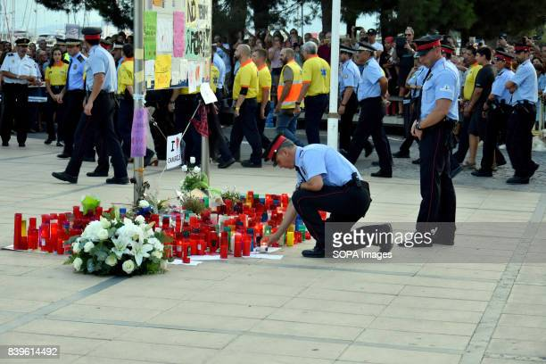 The Catalan police are seen lighting candles in the place where a woman died in the terrorist attack during the wreath for the victims of the...