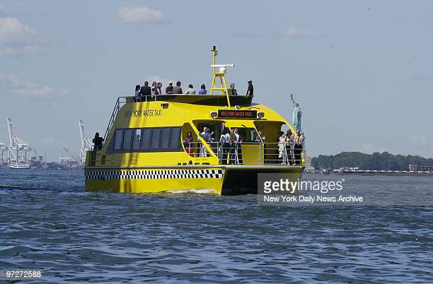 The catamaran Mickey Murphy bright yellow and sporting blackandwhite checks like and old Checker Cab makes its way in a trial run past the Statue of...