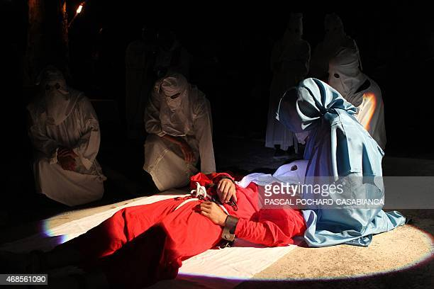 The 'catenacciu' a hooded and chained penitent places his head on the knees of a woman representing the Virgin Mary during a reenactment of the...