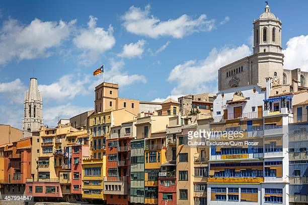 The cathedral and Sant Felix church behind skyline of Girona Town. Catalan independetist flag and houses of the old quarter