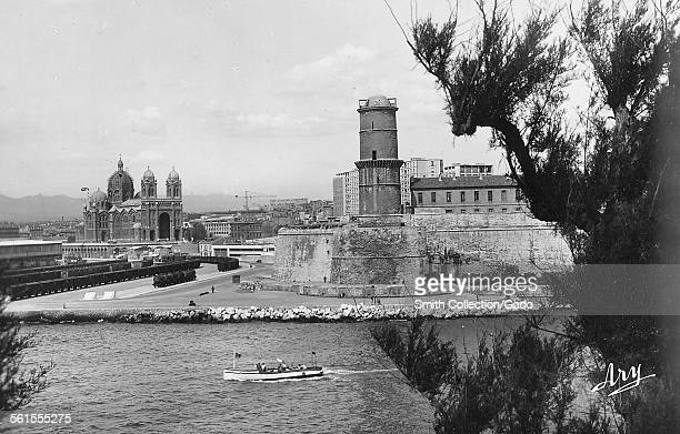 The cathedral basilica of NotreDamedelaGardeand the fort Saint Jean in the port Marseille Cote d'Azur France 1930