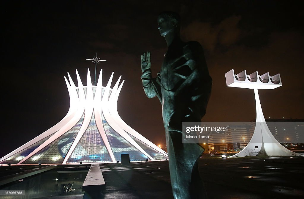 The Cathedral of Brasilia (L) is shown lit at night on October 27, 2014 in Brasilia, Brazil. Brazil's left-wing President Dilma Rousseff was narrowly re-elected yesterday and will serve another four years in Brazil's unique planned capital city. The modernist city was founded in 1960 and replaced Rio de Janeiro as the federal capital of Brazil. The city was designed by urban planner Lucio Costa and architect Oscar Niemeyer and is now a UNESCO World Heritage site.