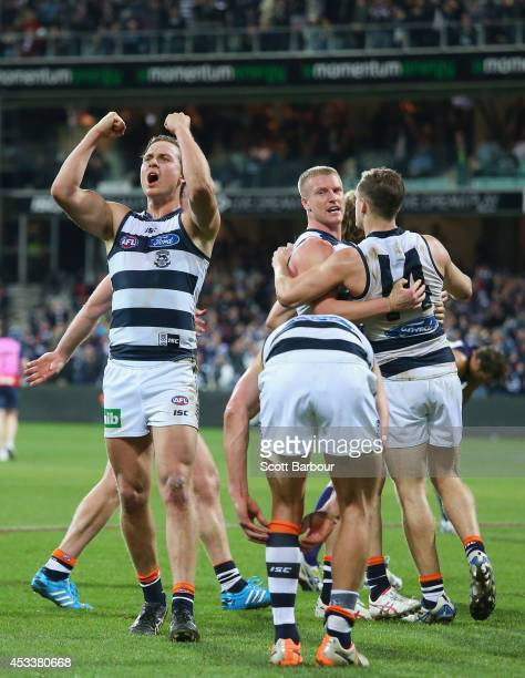 The Cats celebrate victory at the final siren as David Mundy of the Dockers walks away after missing the final shot at goal during the round 20 AFL...